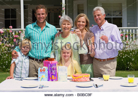 Three generation family celebrating senior woman's '60th' birthday in summer garden in front of house, smiling, - Stock Photo