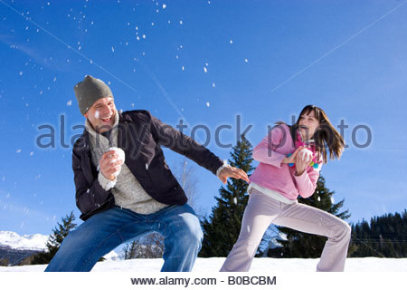 Young couple having snow flight in snow field, laughing, low angle view - Stock Photo