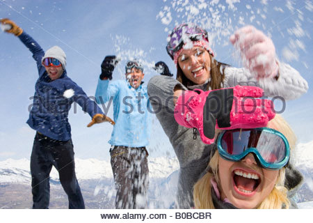 Two young couples having snow fight in snow field, mountain range in background - Stock Photo