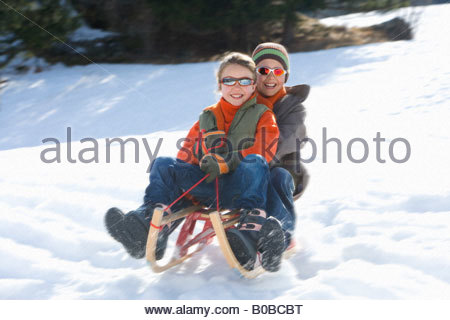 Boy and girl  riding sled down snow slope, wearing sunglasses, smiling, low angle view - Stock Photo