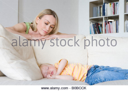 Mother looking at daughter 12-15 months asleep on sofa, close-up - Stock Photo