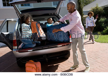 Son and daughter  helping father load luggage in back of car tilt - Stock Photo