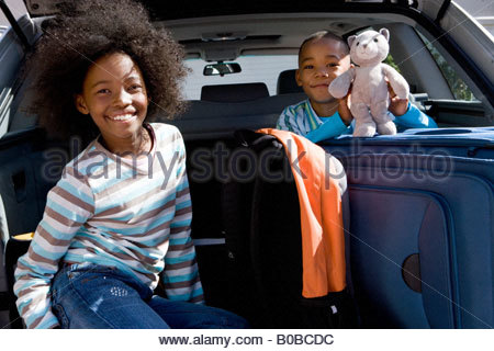 Brother and sister  in back of car with luggage, boy holding toy, smiling, portrait - Stock Photo
