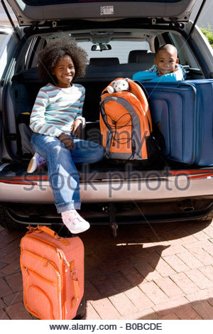 Brother and sister  in back of car with luggage, smiling, portrait - Stock Photo