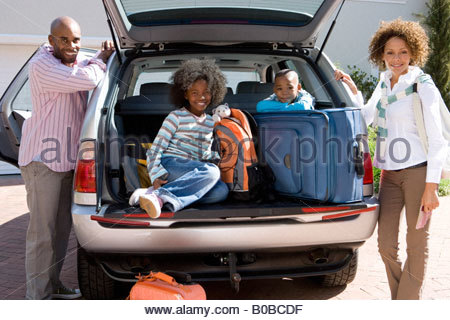 Man and woman by son and daughter  in back of car with luggage, smiling, portrait - Stock Photo