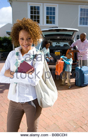 Woman in driveway with passports, family loading luggage into car in background, smiling, portrait - Stock Photo