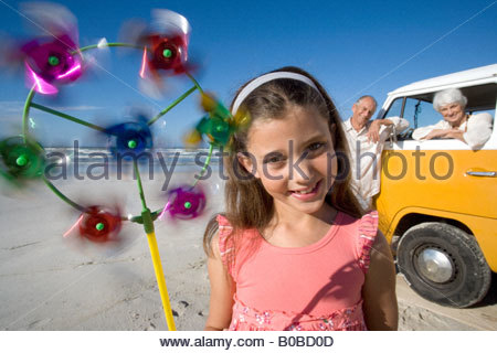 Girl  with pinwheel on beach, grandparents and camper van in background, smiling, portrait - Stock Photo