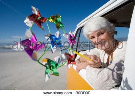 Senior woman holding pinwheel out window of camper van on beach, smiling, portrait - Stock Photo