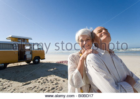 Senior woman embracing senior man from behind on beach by camper van, smiling, portrait - Stock Photo