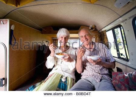 Senior couple eating breakfast in back of camper van, smiling, portrait - Stock Photo