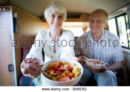 Senior couple eating breakfast in back of camper van, smiling, close-up of bowl differential focus - Stock Photo
