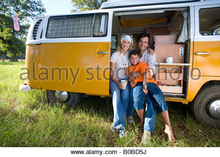 Family of three in camper van, boy 10-12 on father's lap, smiling, portrait - Stock Photo