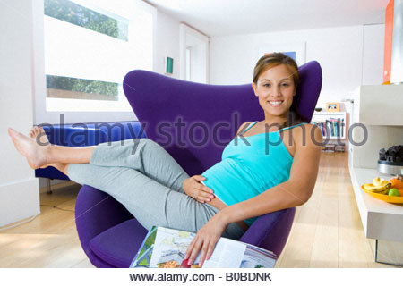 Young pregnant woman in armchair with magazine, smiling, portrait - Stock Photo