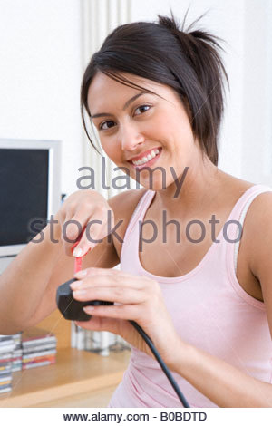 Young woman with screwdriver and plug, smiling, portrait, close-up - Stock Photo