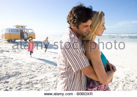 Man embracing woman on beach, children 5-9 in background, side view - Stock Photo