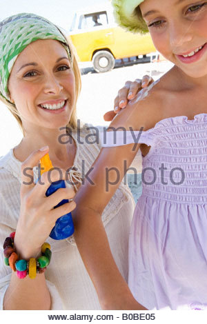 Mother applying sunscreen to daughter  on beach, smiling, low angle view - Stock Photo