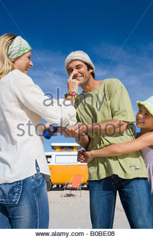 Family of three on beach, woman applying sunscreen to man's nose, daughter  embracing father, low angle view - Stock Photo