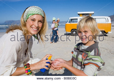 Family of four on beach, mother applying sunscreen to son , smiling, portrait - Stock Photo