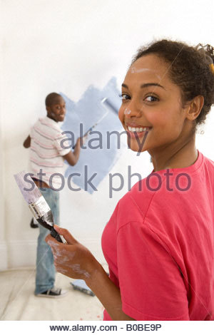 couple decorating christmas tree young couple home decorating woman with paintbrush in foreground smiling portrait stock