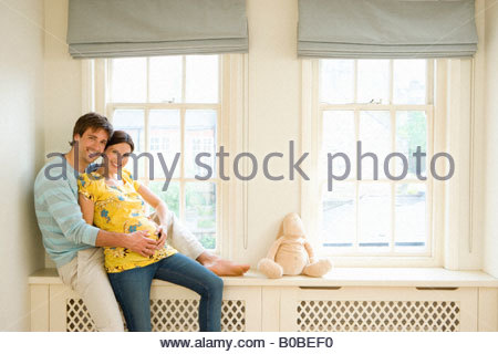 Young couple on windowsill, man embracing pregnant woman, smiling, portrait - Stock Photo
