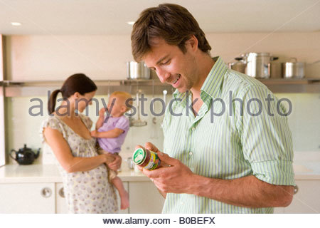 Young couple in kitchen, pregnant woman with baby girl 6-9 months, man looking at baby food label - Stock Photo