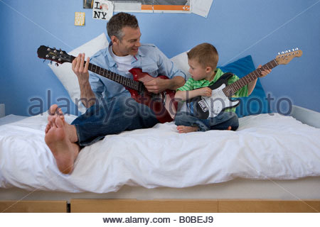 Father and son 2-4 on bed with electric guitars, looking at each other - Stock Photo