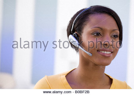 Woman in headset, smiling, close-up - Stock Photo