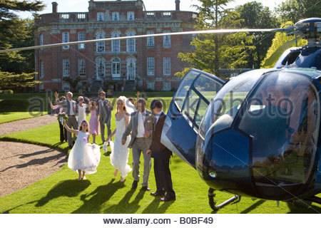 Wedding guests waving at bride and groom by helicopter - Stock Photo