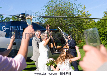 Bride and groom by helicopter waving to wedding guests - Stock Photo
