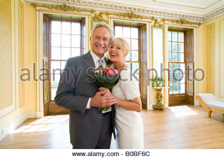 Senior bride and groom with bouquet of flowers indoors, smiling, portrait - Stock Photo
