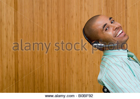 Businessman wearing headset leaning back in chair, smiling, portrait, close-up, side view - Stock Photo