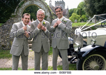 Groom and groomsmen adjusting ties by vintage car, church in background, smiling, portrait - Stock Photo