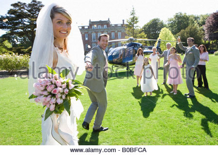 Groom leading bride towards helicopter, smiling, portrait of bride - Stock Photo