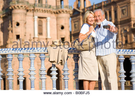 Senior couple taking photograph of themselves by castle - Stock Photo