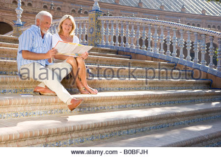 Senior couple looking at tourist map on steps of bridge, low angle view - Stock Photo