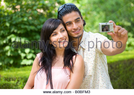 Young couple taking photograph of themselves, close-up - Stock Photo