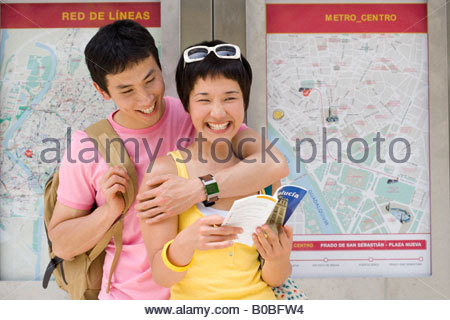 Man embracing woman with leaflet by maps on wall, smiling, close-up - Stock Photo