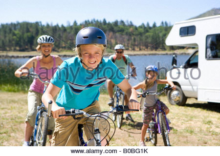 Family of four on bicycles by motor home, close-up of boy 10-12 - Stock Photo