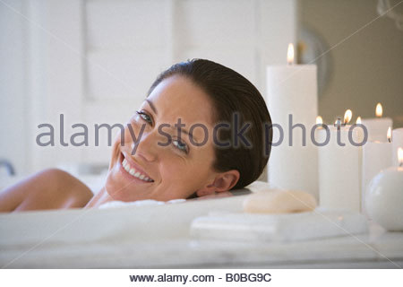 Young woman in bubble bath by candles, smiling, portrait - Stock Photo