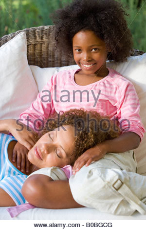 Mother lying asleep in daughter's  lap on sofa - Stock Photo