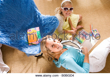 Mother and daughter  on floor by chair doing homework, girl wearing sunglasses, smiling, portrait, elevated view - Stock Photo