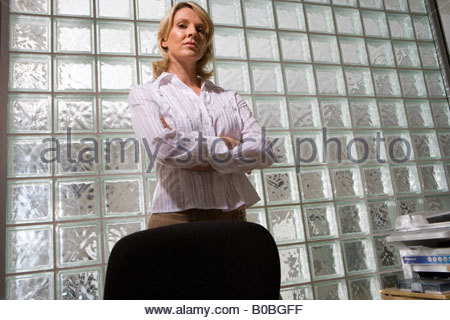 Businesswoman with arms crossed by glass block wall, portrait, low angle view - Stock Photo