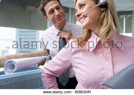 Businessman holding rolls of blueprints smiling at businesswoman wearing headset in office, low angle view - Stock Photo