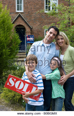 Family of four outside house, boy  with 'for sale' sign, smiling, portrait - Stock Photo