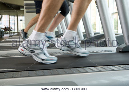 Man running on treadmill, close-up of feet, low section - Stock Photo