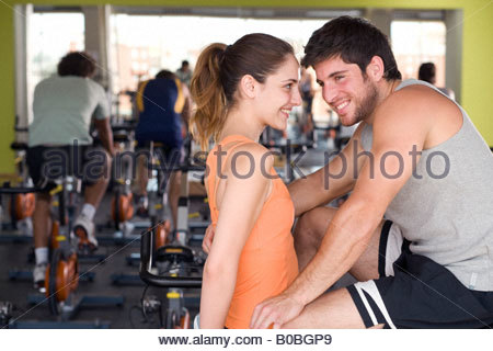 Man and woman smiling at each other in gym, man's arm around woman, side view - Stock Photo