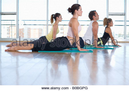 Yoga students in cobra position in class in studio, side view - Stock Photo