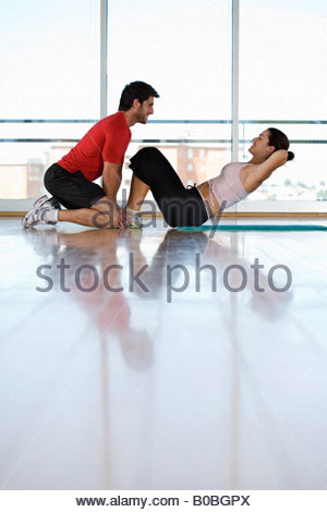 Man helping woman with sit-ups in gym studio, side view - Stock Photo