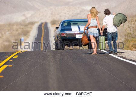 Young couple hitchhiking on desert road, walking towards car, rear view - Stock Photo