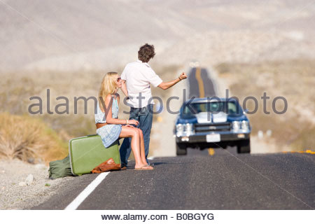 Young couple hitchhiking on desert road, side view - Stock Photo